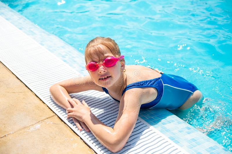Happy little girl in goggles playing in swimming pool Beach resort, summer vacation, travel and tourism concept. Relax stock photo