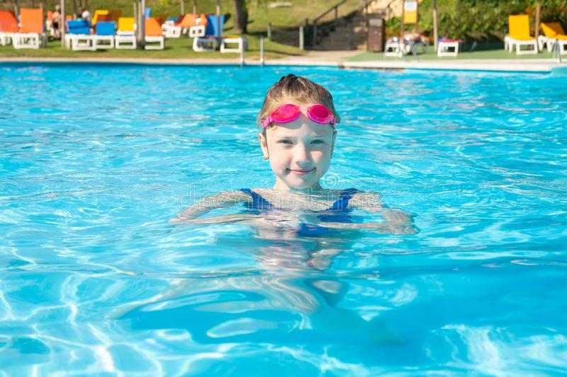Happy little girl in goggles playing in swimming pool Beach resort, summer vacation, travel and tourism concept. Relax royalty free stock image