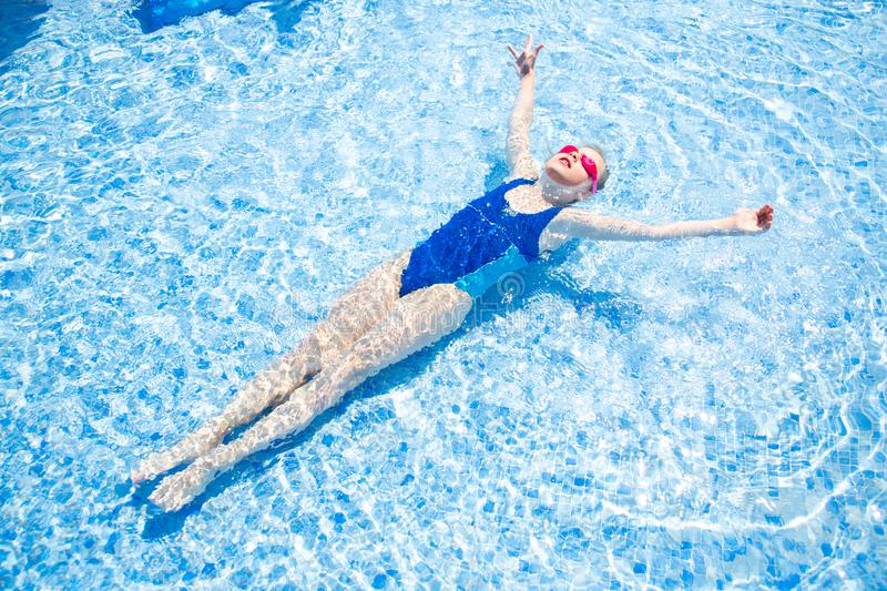 Happy little girl in goggles swim in swimming pool View from above stock image