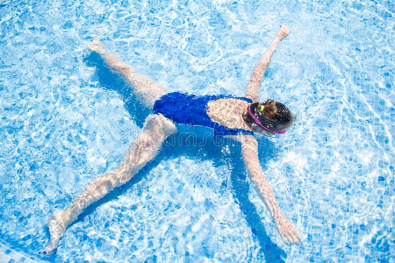 Happy little girl in goggles swim in swimming pool View from above royalty free stock photos