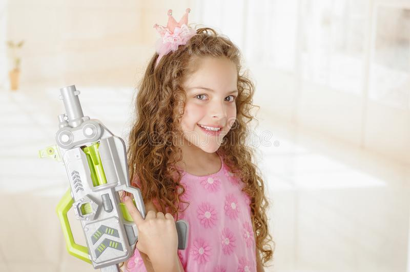 Happy little girl with gun and wearing a pink princess dress stock images