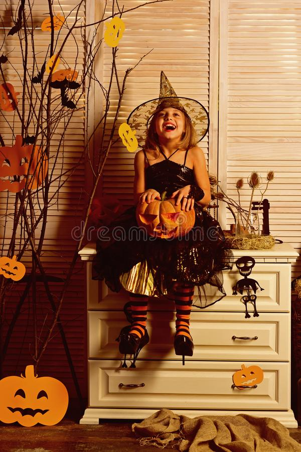 Happy little girl with halloween pumpkin. Wicked little witch. Girl happy smiling on halloween. Prettiest pumpkin in the. Patch. Happy halloween to all stock photo