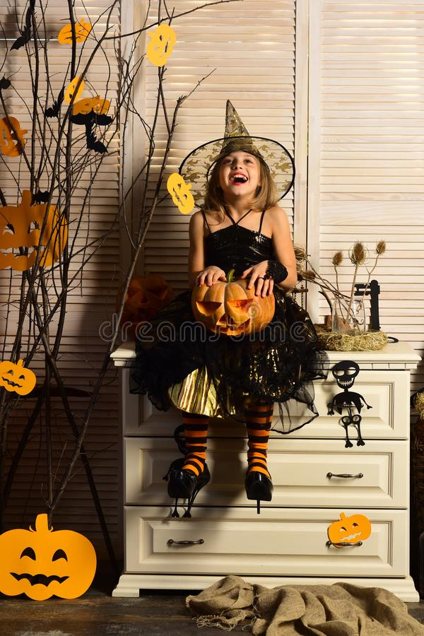 Happy little girl with halloween pumpkin. Wicked little witch. Girl happy smiling on halloween. Prettiest pumpkin in the royalty free stock photos