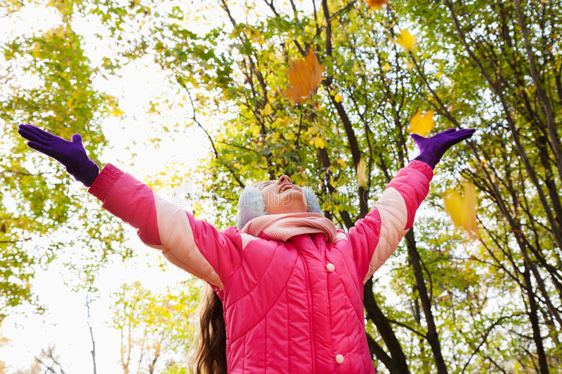 Happy little girl with hands up in autumn park stock photo