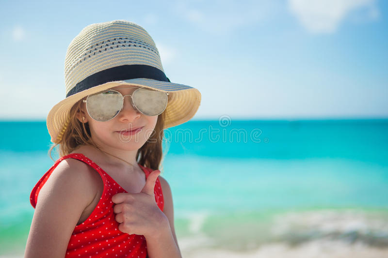 Happy little girl in hat on beach during summer royalty free stock photo