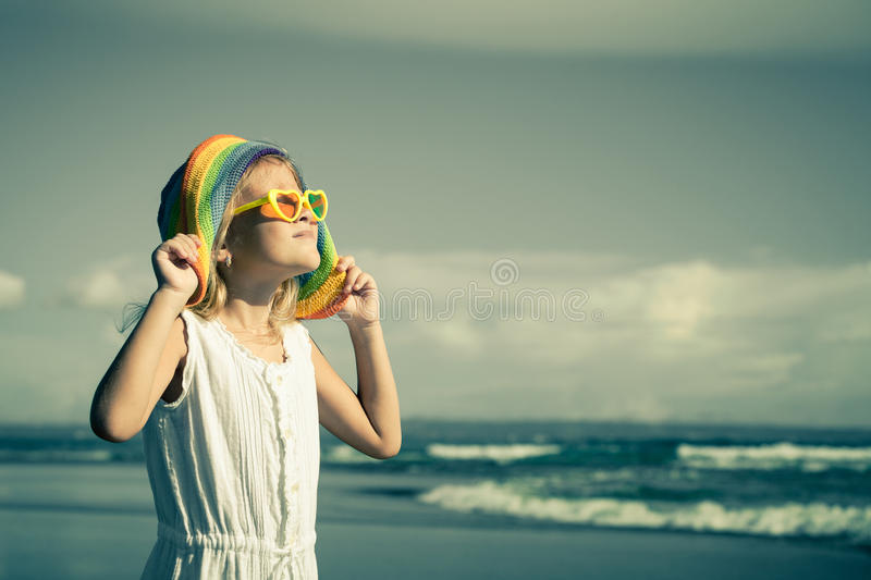 Happy little girl in the hat standing on the beach at the day t royalty free stock photo