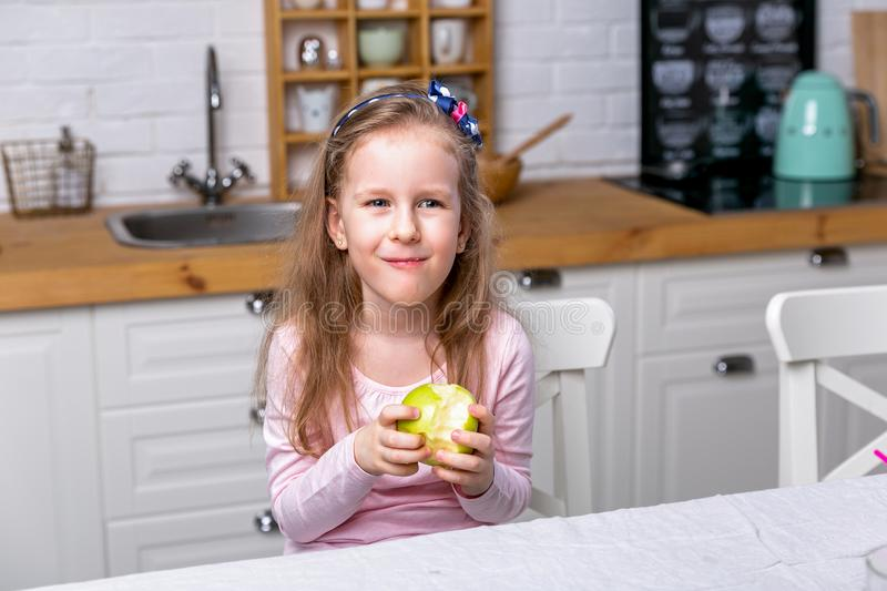 Happy little girl have breakfast in a white kitchen. She eats apple and smiling. Healthy eating stock photos