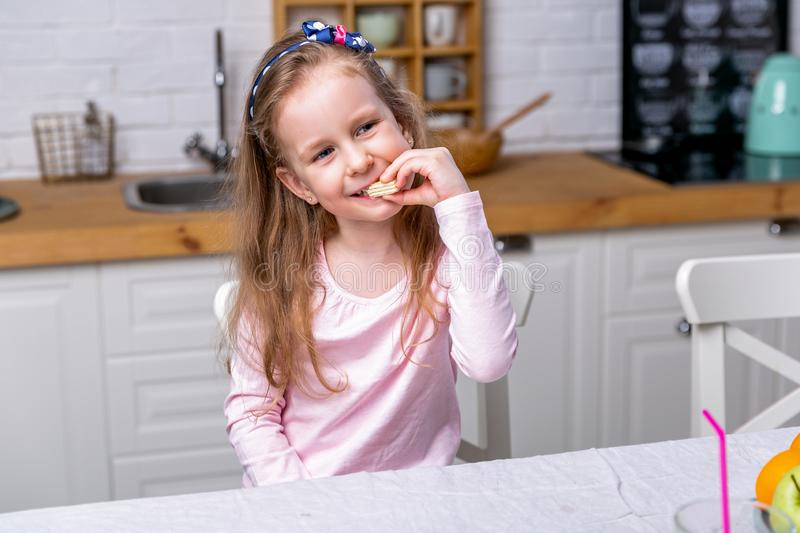 Happy little girl have breakfast in a white kitchen. She eats waffles and smiling. Healthy eating stock photos