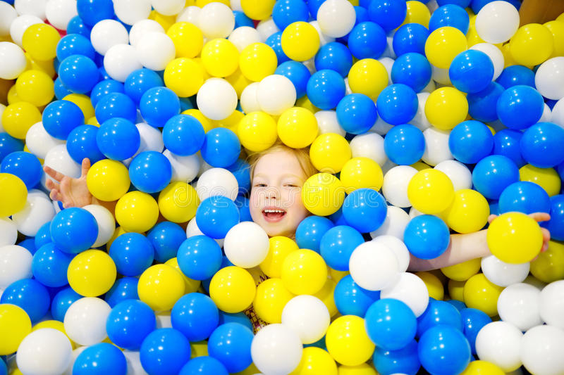 Happy little girl having fun in ball pit in kids indoor play center. Child playing with colorful balls in playground ball pool. Activity toys for little kids royalty free stock photo