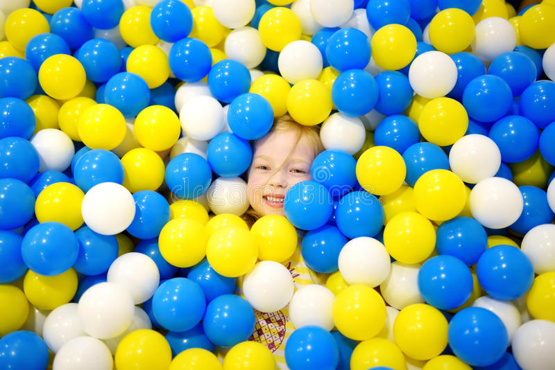 Happy little girl having fun in ball pit in kids indoor play center. Child playing with colorful balls in playground ball pool. stock photo