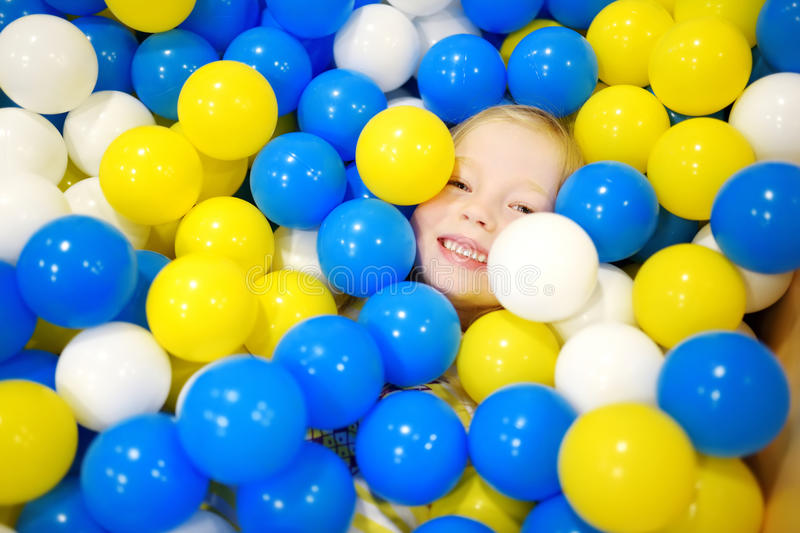 Happy little girl having fun in ball pit in kids indoor play center. Child playing with colorful balls in playground ball pool. Activity toys for little kids stock photo