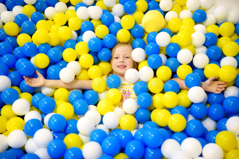 Happy little girl having fun in ball pit in kids indoor play center. Child playing with colorful balls in playground ball pool. Activity toys for little kids stock images