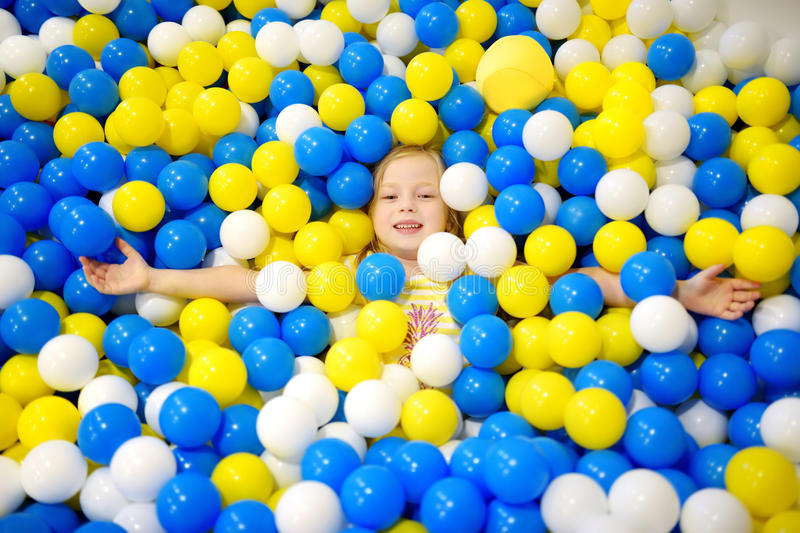 Happy little girl having fun in ball pit in kids indoor play center. Child playing with colorful balls in playground ball pool. Activity toys for little kids stock image