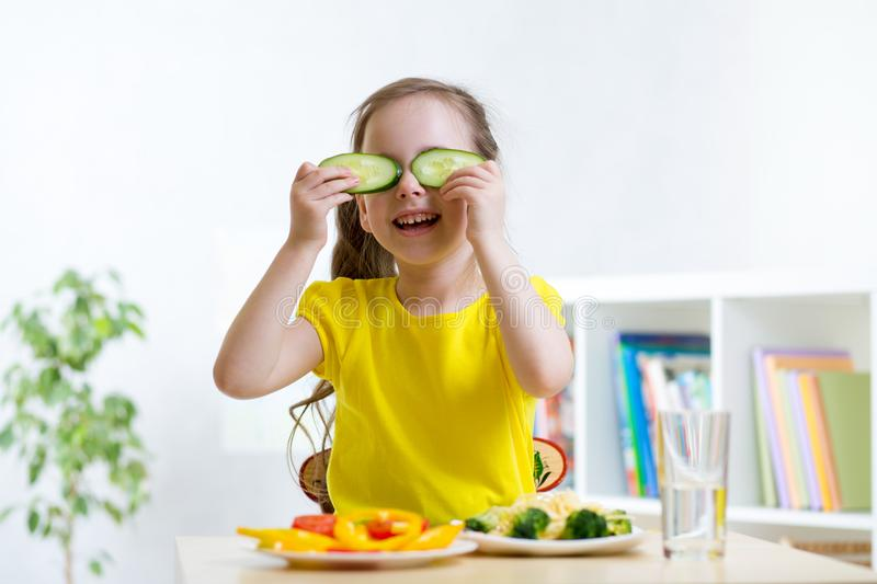 Happy little girl having fun with food vegetables while dinner holds cucumbers before her eyes like in glasses royalty free stock photos