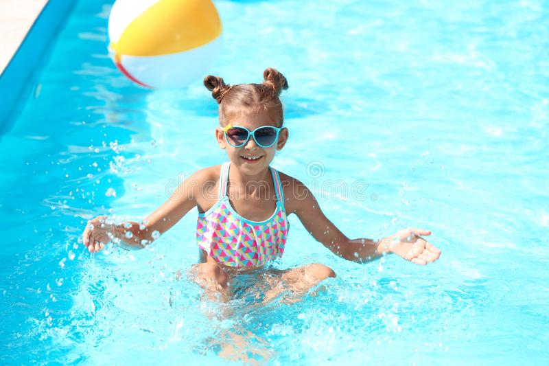 Happy little girl having fun in pool royalty free stock photography