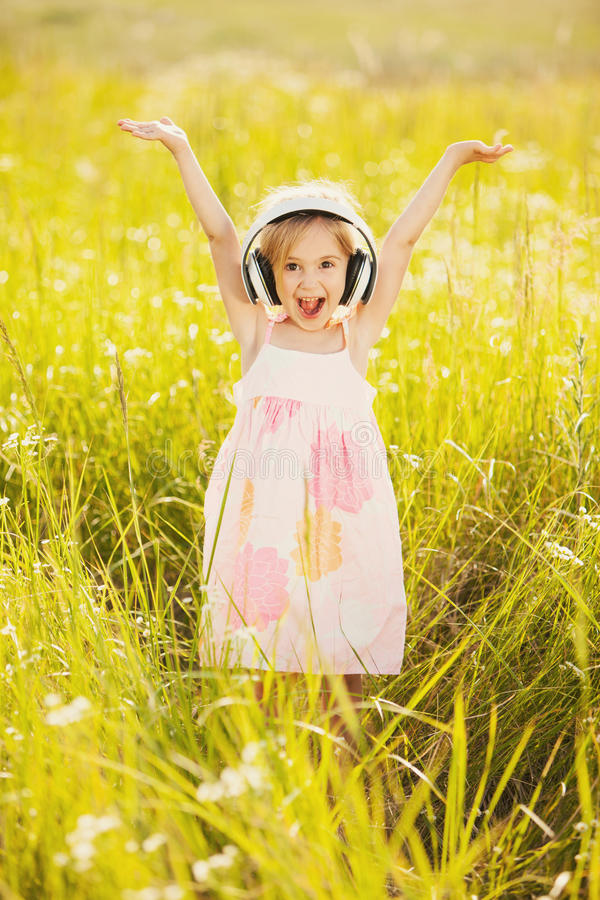 Happy little girl with headphones stock images