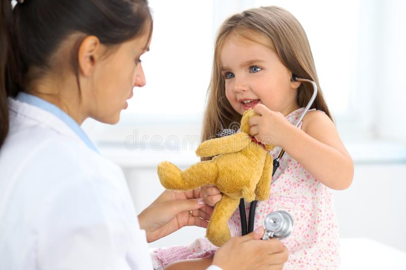 Happy little girl at health exam at doctor office. Medicine and health care concept stock photo