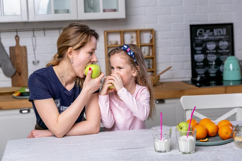 Happy little girl and her beautiful young mother have breakfast together in a white kitchen. They are having fun and eating apples royalty free stock images