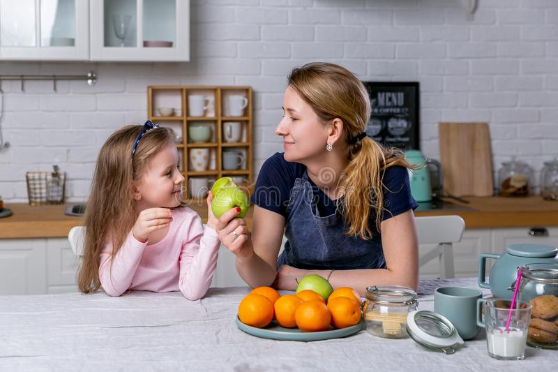 Happy little girl and her beautiful young mother have breakfast together in a white kitchen. They are having fun and eating apples stock photos
