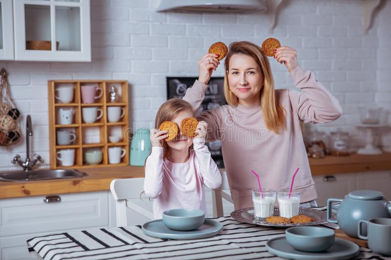 Happy little girl and her beautiful young mother have breakfast together in a white kitchen. They are having fun and playing with stock photos