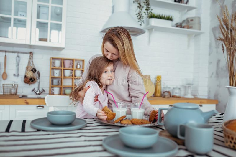Happy little girl and her beautiful young mother have breakfast together in a white kitchen. Mom hugs and kisses daughter. royalty free stock photos