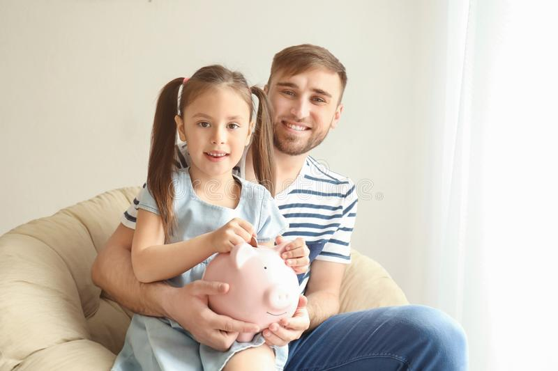 Happy little girl with her father sitting in armchair and putting coin into piggy bank indoors. Money savings concept stock photography