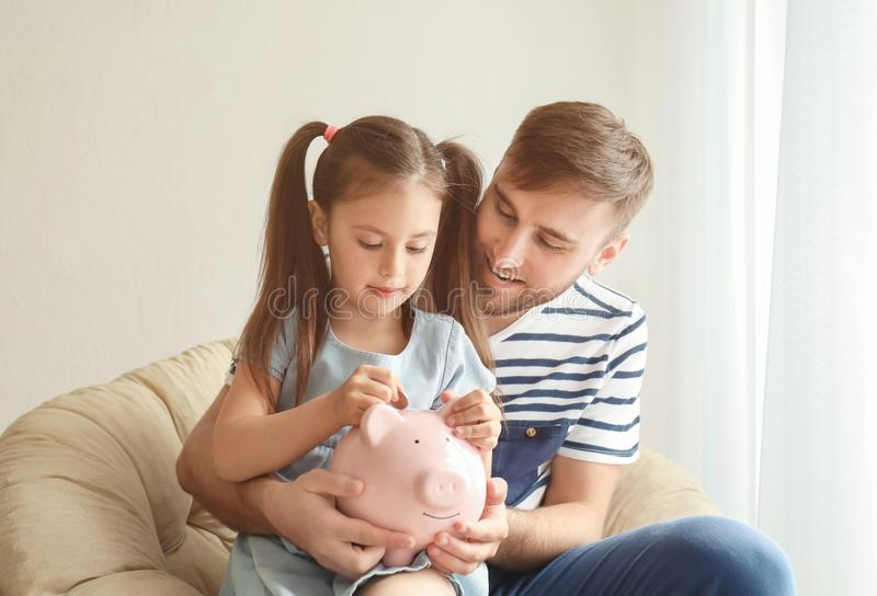 Happy little girl with her father sitting in armchair and putting coin into piggy bank indoors. Money savings concept stock photo