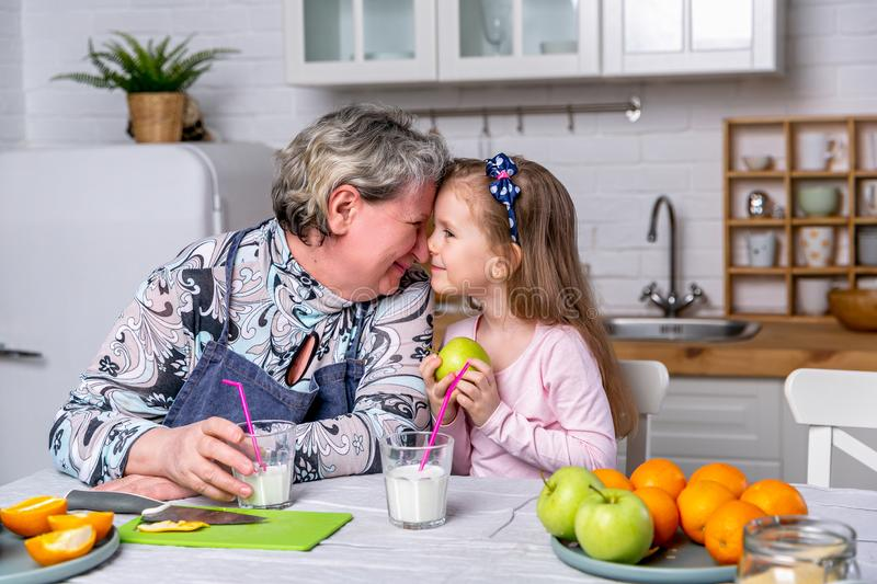 Happy little girl and her grandmother have breakfast together in a white kitchen. They are having fun and playing with fruits. stock photos