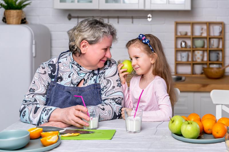 Happy little girl and her grandmother have breakfast together in a white kitchen. They are having fun and playing with fruits. royalty free stock photo