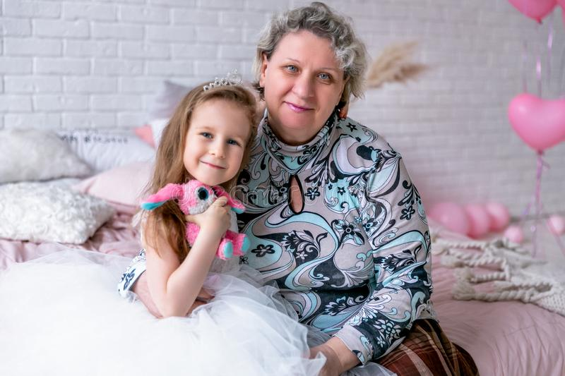 Happy little girl and her grandmother are sitting together and hugging in the bedroom. They are smilling and kissing. Maternal stock photography