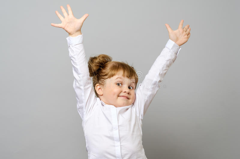 Happy little girl with her hands up stock photos