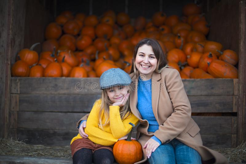 Happy little girl with her mother at the autumn pumpkin patch background royalty free stock photos