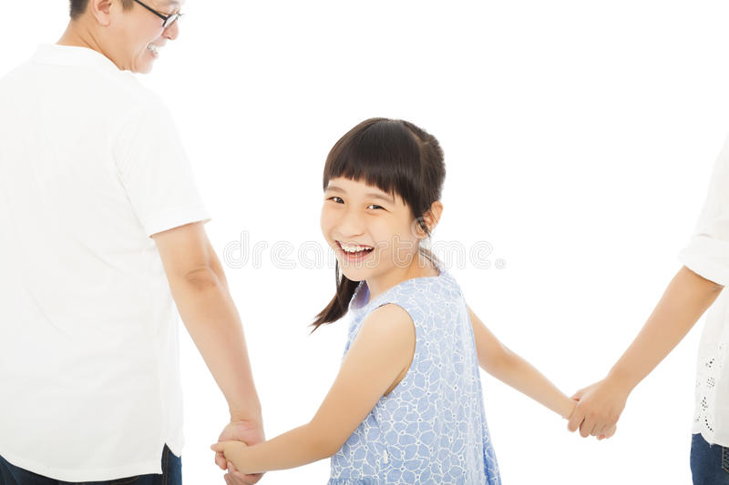 Happy little girl hold parents hands and smiling . stock photo
