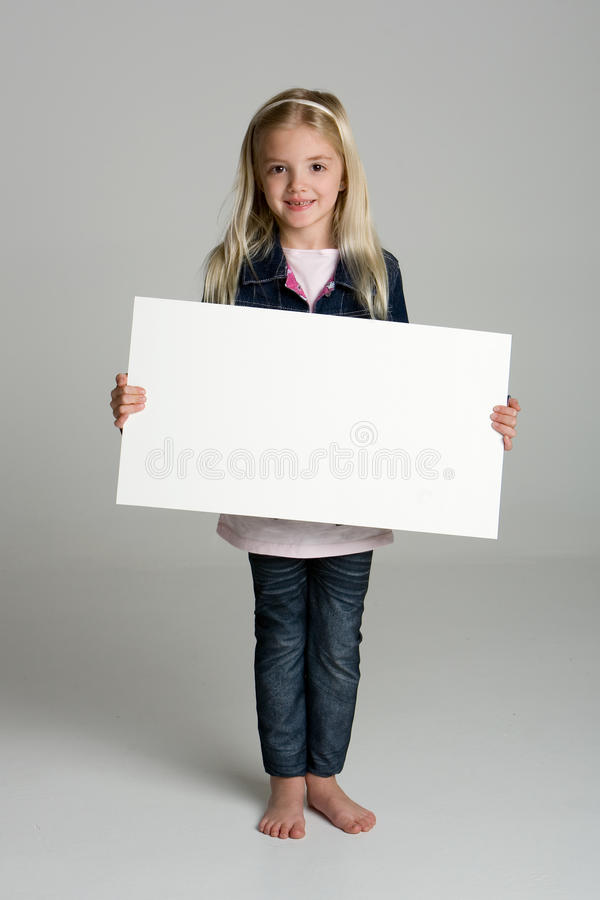 Happy little girl holding a blank sign. Happy little girl isolated on neutral background holding a blank sign royalty free stock images