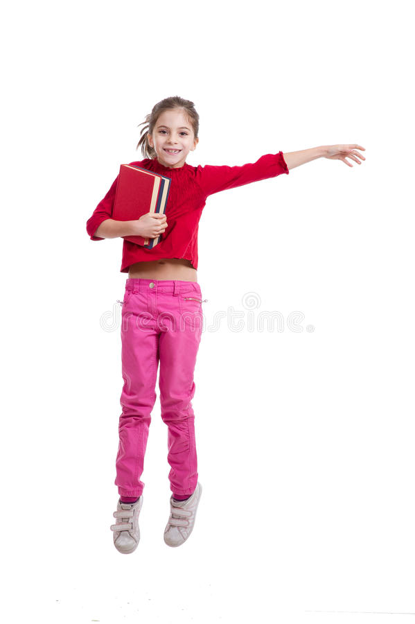 Happy little girl holding books jumping royalty free stock photography