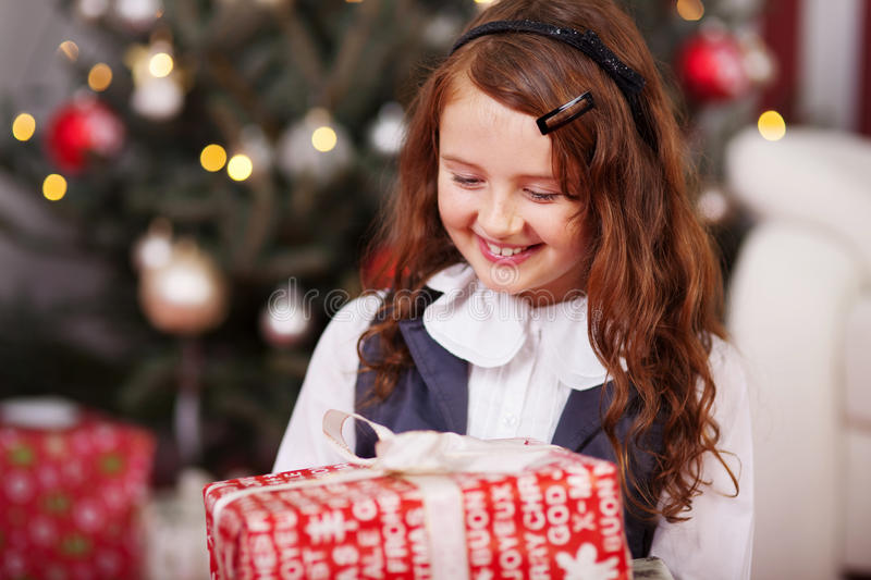 Happy little girl holding a Christmas present stock image