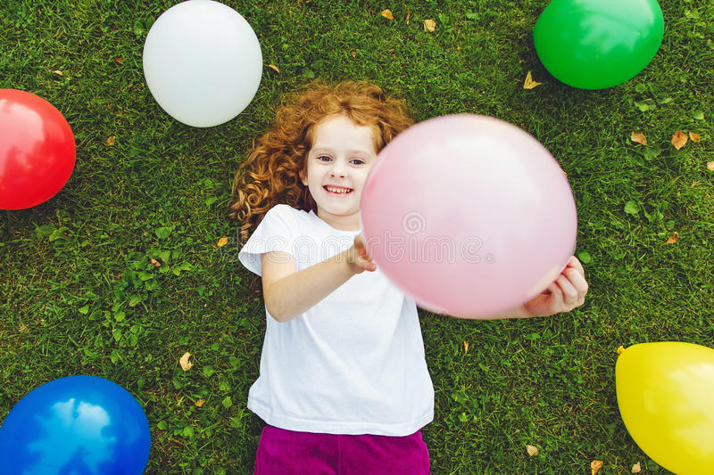 Happy little girl holding colored balloon, lies on green grass a stock photography