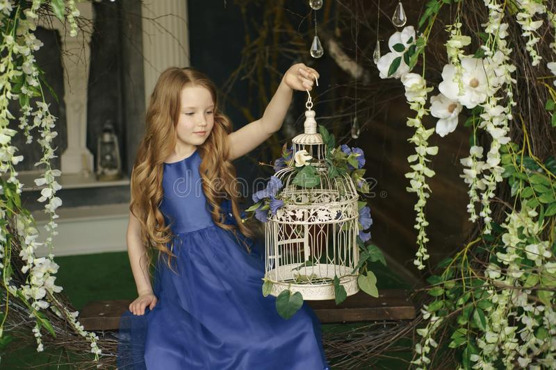 Happy little girl holding decorative bird cage full of flowers. Studio shot in provence style interior royalty free stock photos