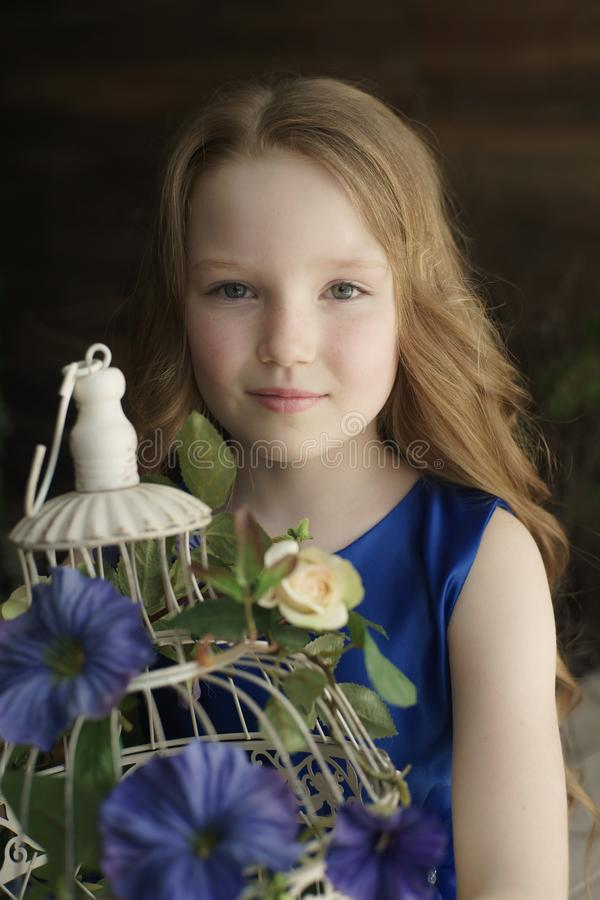 Happy little girl holding decorative bird cage full of flowers. Studio shot in provence style interior stock photography