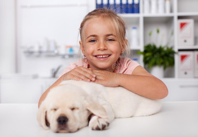 Happy little girl holding her sleeping puppy dog at the veterinary doctor office. Happy little girl holding her sleeping puppy dog and smiling at the veterinary royalty free stock photo
