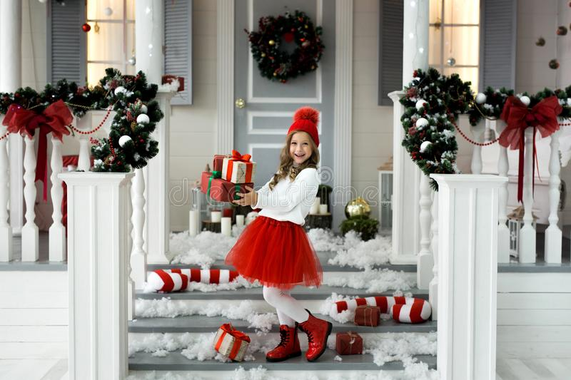 Happy little girl holding a lot of boxes with gifts. winter holidays, christmas and people concept. stock image