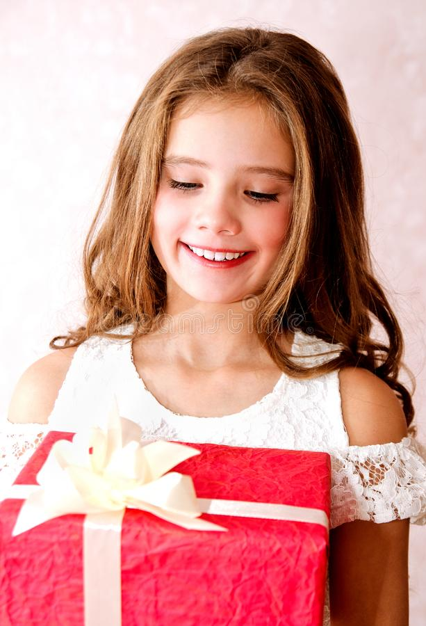 Happy little girl holding red gift box in christmas time stock photo