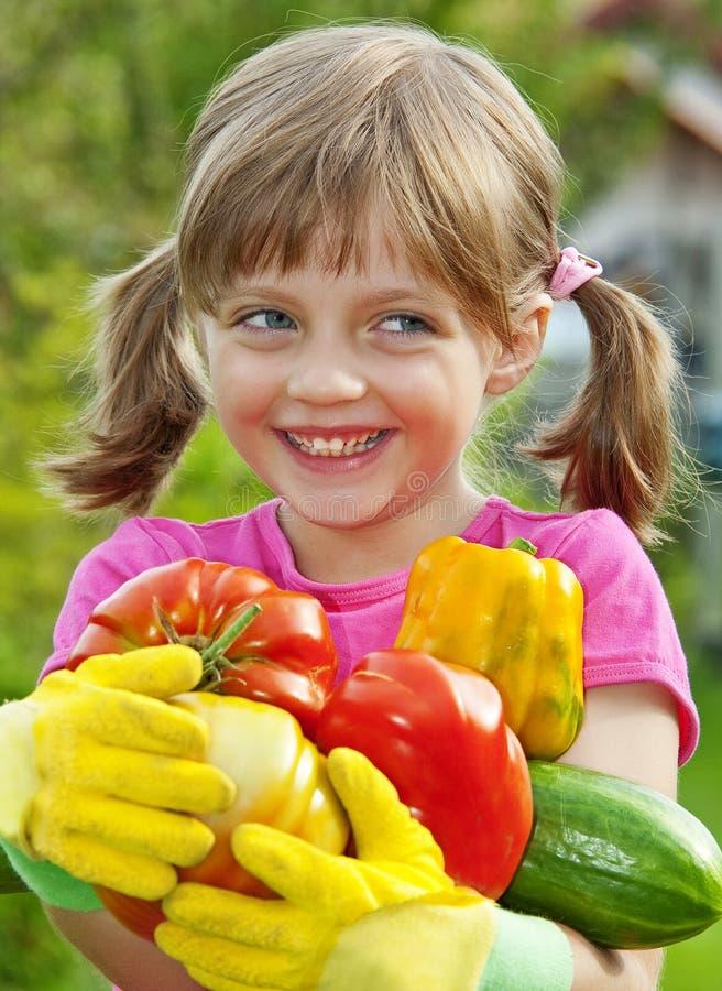 Happy little girl holding vegetables stock image