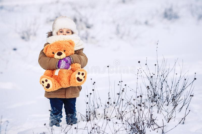Happy little girl holds in her arms an orange teddy bear in winter outside. royalty free stock photography