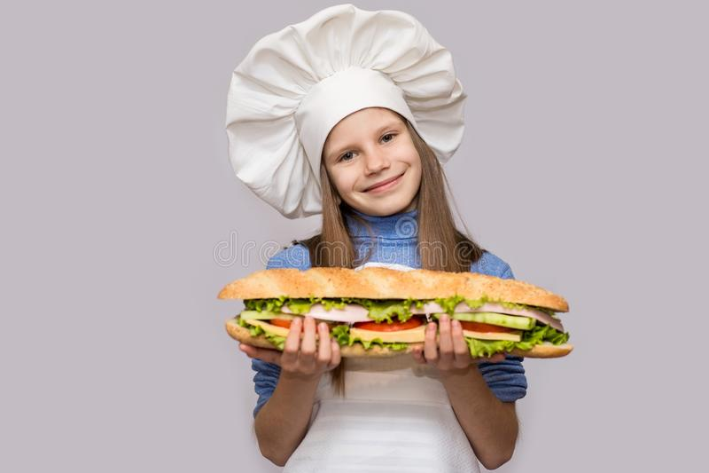 Happy little girl with hot dog and chef uniform isolated on white background stock image