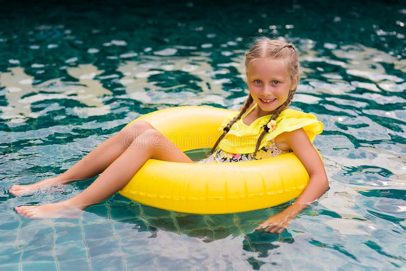 Happy little girl with inflatable rubber circle having fun in swimming pool stock image