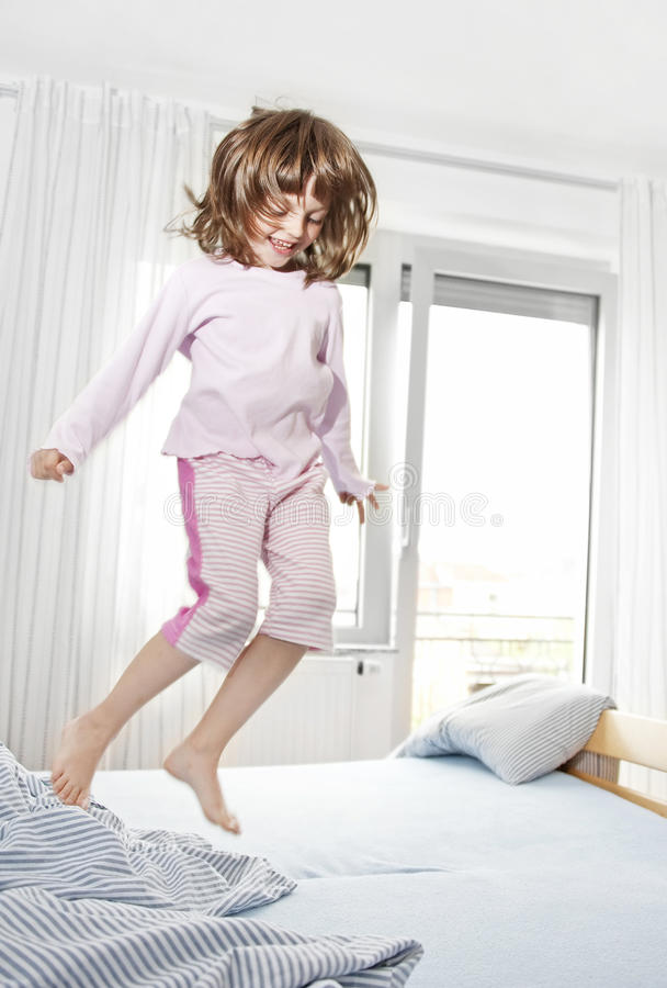 Happy little girl jumping on a bed stock image