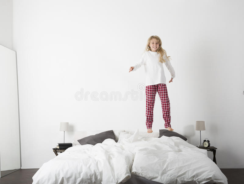 Happy little Girl jumping in bed stock image