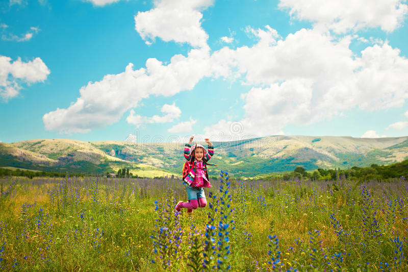 Happy little girl jumping on the field. Cute happy little girl jumping on the spring field. Happiness, lifestyle concept royalty free stock photos