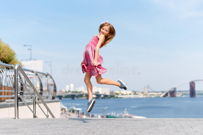 Happy little girl jumping and flying outdoors near the river embankment. Summer vacation and children`s games to spend royalty free stock photo